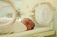 newborn baby in far-infrared-heated incubator