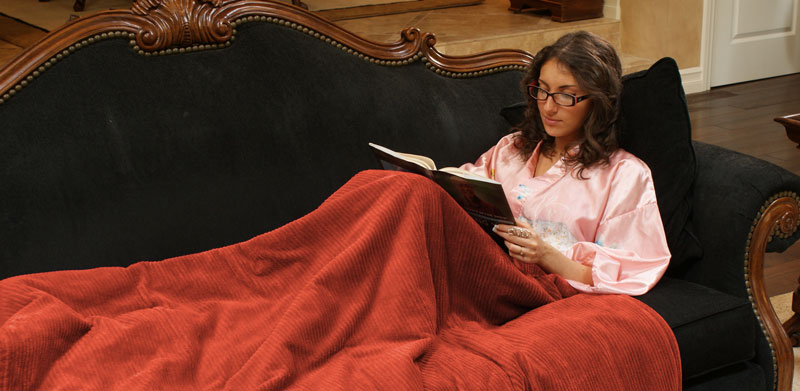Girl reading on sofa while covered in a BioSmart Electric Infrared Blanket